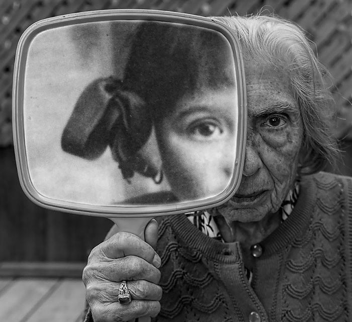 twarz dziewczynki odbija się w lustrze trzymanym przez starszą kobietę