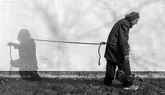 cień ciągnie starszą kobietę obwiązaną sznurem w pasie